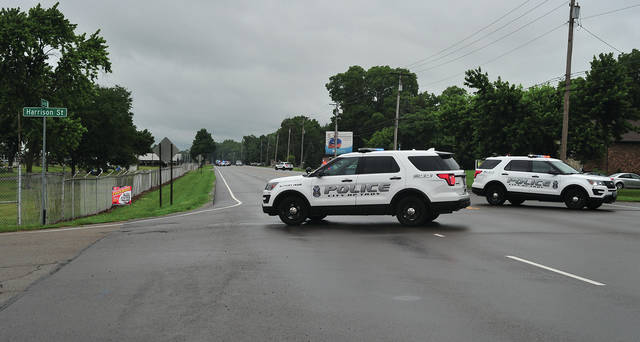 Mike Ullery | AIM Media Midwest A pair of Troy police cruisers block County Road 25-A at Harrison Street on Thursday evening, as an incident involving a gun unfolds down the road. The highway was closed to traffic in both directions as Miami County Sheriff's deputies and Troy Police worked the incident.