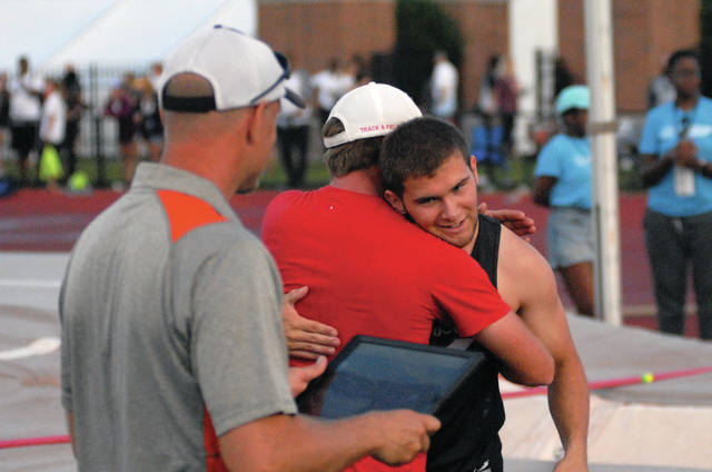 David Fong/Troy Daily News Covington's Jett Murphy embraces Newton coach Nick Rhoades after clearing the winning height in the pole vault, claiming a Division III state championship Friday at Jesse Owens Memorial Stadium.