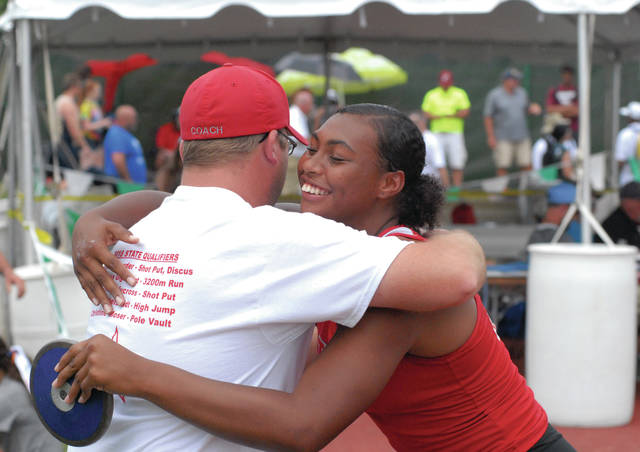 David Fong/Troy Daily News Troy's Lenea Browder embraces coach Kurt Snyder after winning a state championship in the discus at the Division I state meet Saturday at Jesse Owens Memorial Stadium.