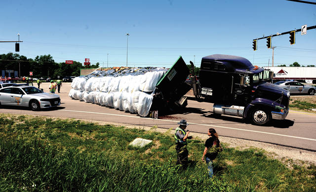 Mike Ullery   Daily Call A trooper from the Piqua Post of the Ohio State Highway Patrol talks to a passenger in a semi whose trailer overturned with a load of bagged mulch at the intersection of East Ash Street (U.S. Route 36) and I-75 in Piqua on Monday afternoon.