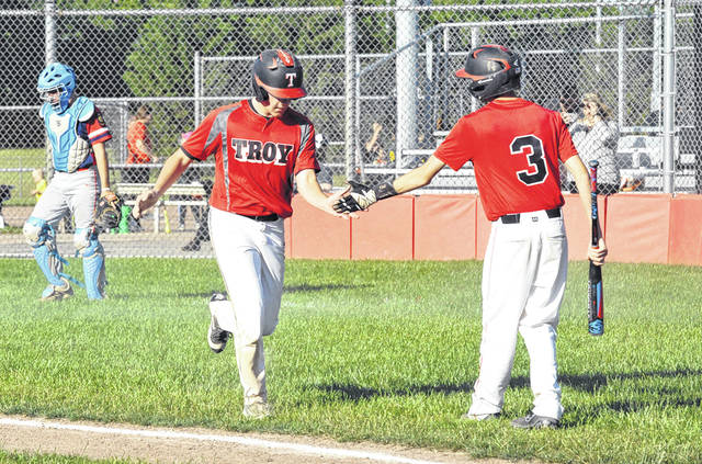 Josh Brown/Troy Daily News Troy Post 43's Nick Hundley is congratulated by teammate Austin Kendall (3) after he scored a run during a doubleheader against Pemberville Legion Monday at Duke Park.