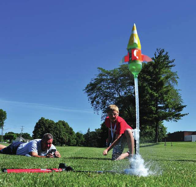 Mike Ullery | Daily Call Brady Wenning, 10, of Anna launches his water bottle rocket as Camp Excel director Tony Trapp shoots video of the launch at Camp Excel 2018 at the Upper Valley Career Center on Wednesday. 104 students from around the area attended this year's camp.
