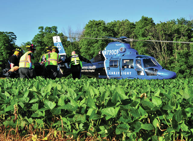 Medics and firefighters from Union Township and West Milton carry a crash victim to CareFlight following a single-vehicle rollover crash on Kessler Frederick Road on Thursday evening.