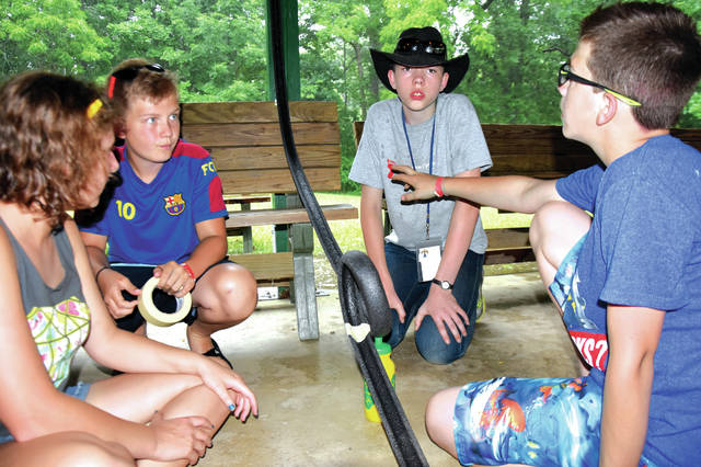 Cody Willoughby | Troy Daily News Counselor Pami Parke assists Luke Brunke of Troy, Isaac Hess of Laura, and Nate Bailey of Tipp City in the construct of a functional marble roller coaster during daily activities on Wednesday at Indian Hills 4-H Camp in Pleasant Hill.
