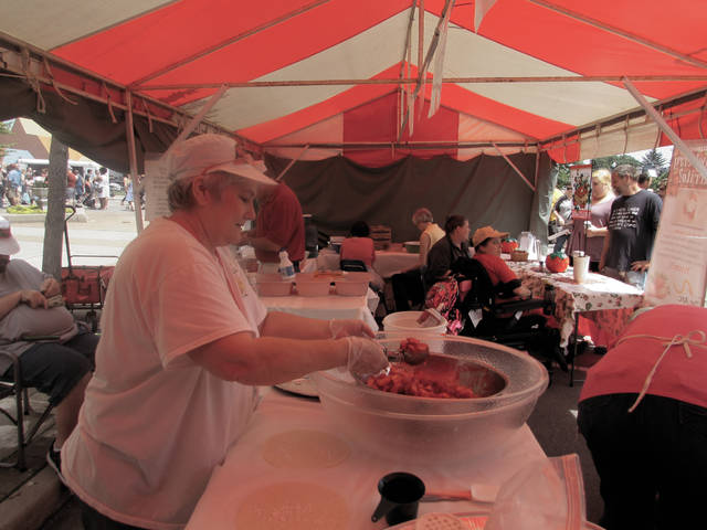 Rosemary Saunders, an organizer with the Arc of Miami County, dishes up strawberry filling for their famous strawberry burritos in downtown Troy