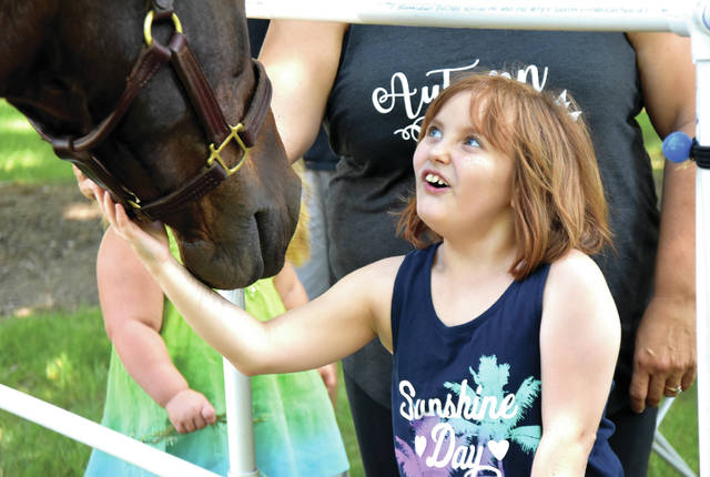 Cody Willoughby | Troy Daily News Lyla Fullerton, 9, of Tipp City meets a therapy horse during the autism awareness open house held by the Tipp City Police Department on Saturday in Tipp City Park.