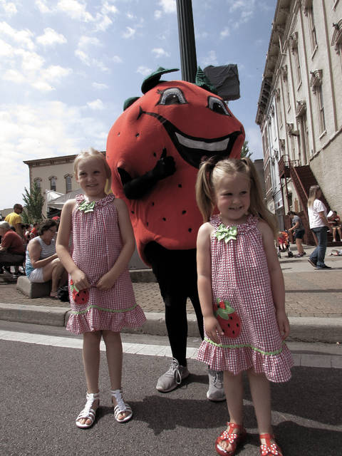 Melanie Yingst | Troy Daily News From left, Baylee Sue Bigelow and sister Ellee Mae pose with the Strawberry Festival mascot in downtown Troy on Saturday morning.