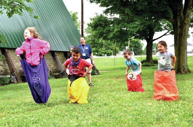 Cody Willoughby | Troy Daily News Camp Chaplain Ed Ellis (background) encourages the young competitors in a sack race during Camp Courageous on Monday in Ludlow Falls.
