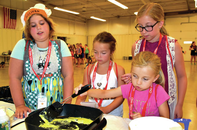 "Cody Willoughby | Troy Daily News Left to right, Sullivan Anderson of Troy, Elizabeth Shelton of Tipp City, and Riley Blair and Grace Craven of Fletcher prepare scrambled eggs for breakfast burritos during ""Miami County Junior Chefs,"" a special program hosted by the Ohio State University Extension at Miami County Fairgrounds on Tuesday."