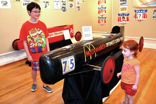 "Cody Willoughby | Troy Daily News Jason and Mackenzie Dollan, 9 and 2, of Troy observe the newly displayed soap box derby cars on Friday at Troy-Hayner Cultural Center. The new exhibit, entitled ""Racing Around Town: The Soap Box Derby,"" features memorabilia and artifacts from The Troy Historical Society, and will be on display at the center until Sunday, July 29. For more information, visit www.troyhayner.org."