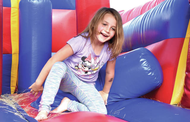 Cody Willoughby | AIM Media Midwest Emma Hostutler, 5, of Urbana traverses the inflatable obstacle course, sponsored by True Life Community Church, during the 42nd annual Troy Strawberry Festival on Saturday.