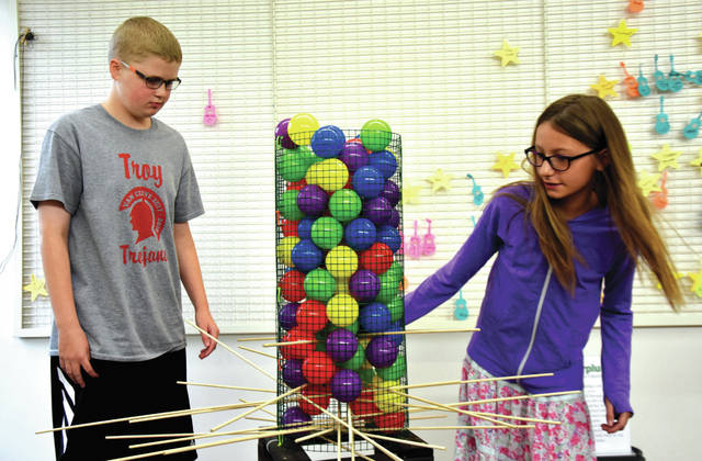 "Cody Willoughby | Troy Daily News Connor Roane and Brianna Baxter of Troy compete in ""Life Size Kerplunk,"" one of many games blown up in size during ""Life Size Games for Teens"" at Troy-Miami County Public Library on Thursday. The event was free to students grades 6-12. For more information on summer library events, visit www.tmcpl.org."