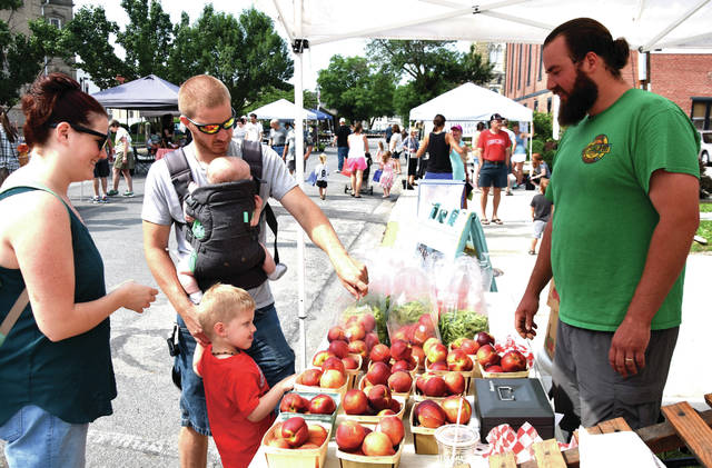 Cody Willoughby | Troy Daily News Brent and Gretchen Wehrley, along with Silas, 3, and Ephraim, 5 months, purchase produce from Joe Fulton of Fulton Farms during the Downtown Troy Farmer's Market on Saturday.