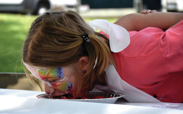 Bethany Hinkle scarfs down her pie during the Strawberry Pie-Eating Contest on Saturday at the 42nd Annual Strawberry Festival in Troy.