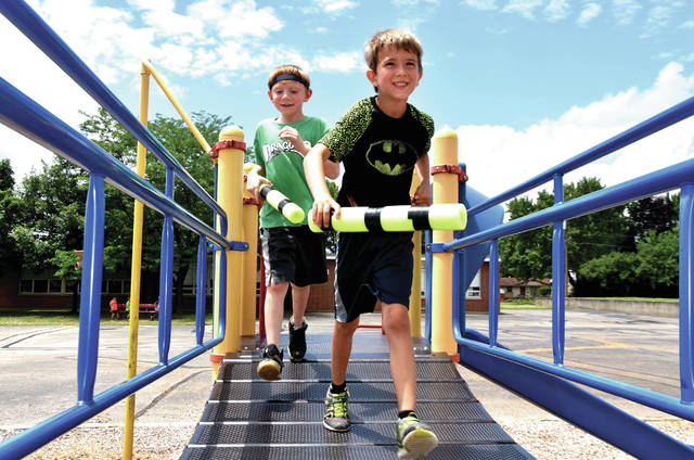 Cody Willoughby | Troy Daily News Caleb Bridges, 6, and Karter Cruea, 7, of Troy, run across the bridge on the playground equipment at Cookson Elementary School during the Playground Program on Wednesday.
