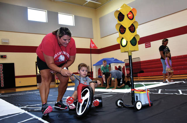 Cody Willoughby | Troy Daily News Milton-Union educator Jenn Shade assists Isaac Hoover during Safetytown activities on Thursday at Milton-Union Elementary School in West Milton.