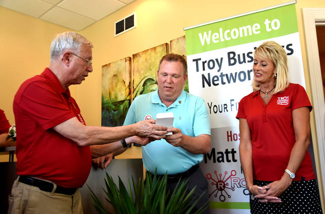 Cody Willoughby | Troy Daily News Your Financial Future owner Matt McCray, center, accepts a medallion from Mayor Mike Beamish and Troy Chamber of Commerce co-chairperson Carrie Kendall during the business' open house on Friday in Troy.