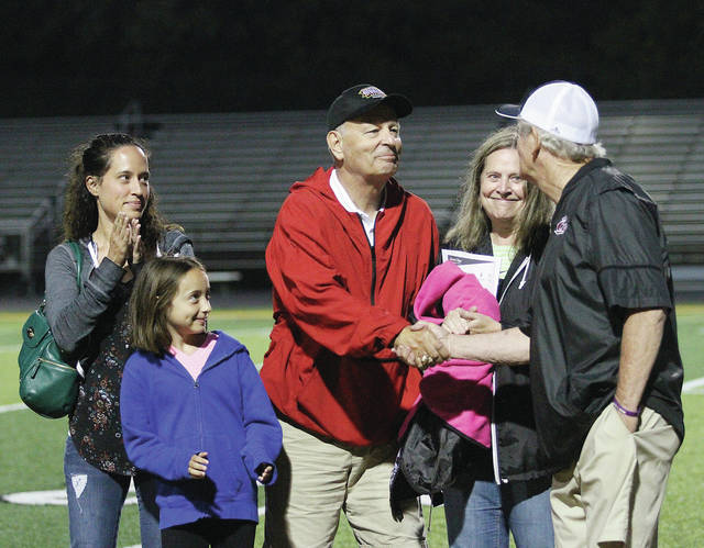 Luke Gronneberg | AIM Media Midwest Former Troy High School assistant football coach Tom Massie (center) is congratulated as he is inducted into the Miami Valley Football Coaches Association Assistant Coaches Hall of Fame last weekend during the MVFCA All-Star Game at Centerville High Schoo.