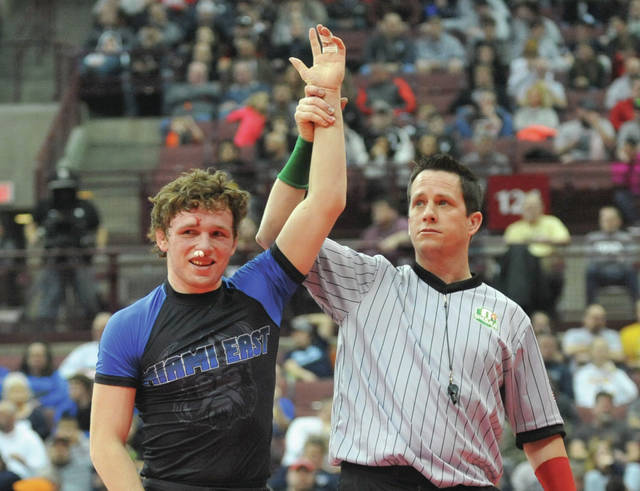 Josh Brown | Miami Valley Sunday News file photo Miami East's Graham Shore (left) has his hand raised after capturing a state wrestling title last winter.