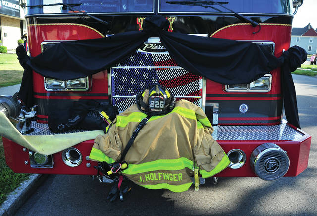 Troy firefighter Jason Holfinger's gear rides on the front of Troy Tanker 1 in honor of the firefighter who passed away nearly one week ago.