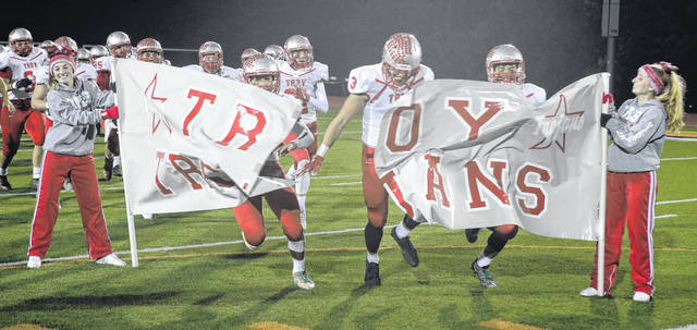 File photo courtesy Lee Woolery | Speedshot Photo The Troy Trojans break through the banner before their first-round playoff game at Anderson last year.