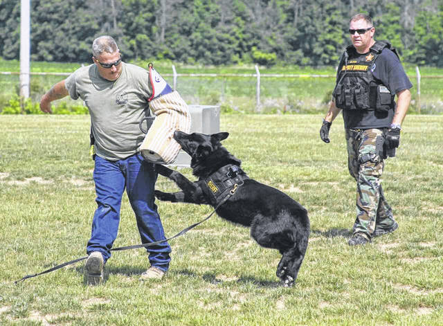 """John Zovac (L), from the South West Regional K9 Group, plays """"decoy"""" and is subdued by """"Colt,"""" a police dog. Colt is handled by Frank Bleigh (R), of Sidney. Both Colt and Officer Bleigh are members of the Shelby County Sheriff's Department. The dog was used in a Critical Response Drill hosted by Airstream, Inc., of Jackson Center."""