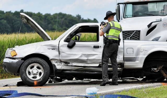 An Ohio State Trooper takes photos of a pick-up truck that was involved in a two-vehicle crash on Thursday afternoon on County Road 25A near Wells Road north of Anna. One person was transported to a Dayton-area hospital by Careflight.