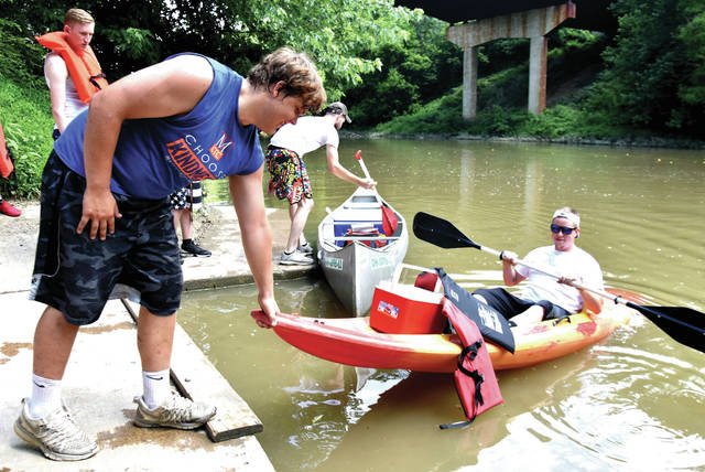 Cody Willoughby | Troy Daily News Employee Hunter Ross assists Logan Peters of Vandalia in lowering his kayak into the Stillwater River at the Barefoot Canoe loading area in West Milton. The establishment is one of several in the Miami County area that offers rentable canoes, kayaks, tubes, and more throughout the summer season. For more information, visit www.barefootcanoe.com.