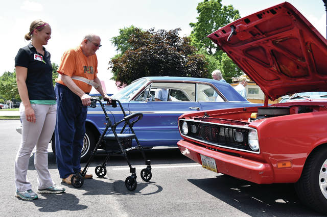 Cody Willoughby | Troy Daily News Occupational therapist Sarah Hess and Fred Pelledier admire a coterie of classic cruisers during the car show on Wednesday at SpringMeade Health Center in Tipp City.