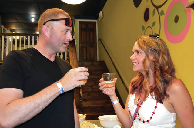 "Cody Willoughby | Troy Daily News Ted and Katy Painter of Tipp City sample rose cider at Living Simply Soap during the ""Red, White, and Brews"" beer crawl on Friday in Tipp City."