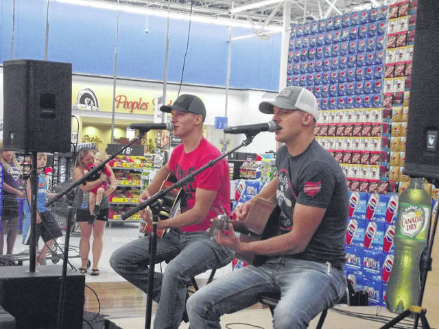 Jared, left, and Justin Younce, also known professionally as ReFlektion, perform at Sidney Walmart Thursday. The duo will be performing on the Hometown Honky Tonk Stage Saturday at Country Concert.