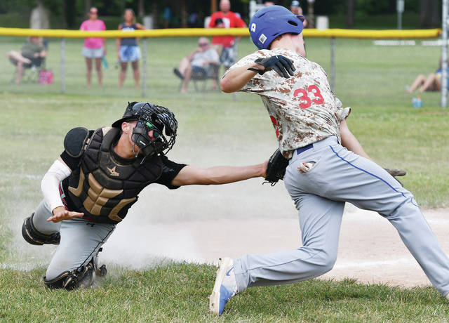Luke Gronneberg | AIM Media Midwest Troy's Andy Wargo, left, tags out Sidney Post 217's Dion Puthoff at home at Custenborder Field Sunday.