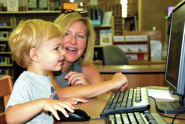 Cody Willoughby | Troy Daily News Dean Scozzari, 2, of Troy, with mother Lindsay, engages in educational games on the computer on Thursday at Troy-Miami County Public Library. Interactive games are an effective tool recommended in helping kids to retain education from the previous school year during the summer months.