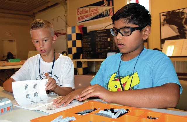 Cody Willoughby | Troy Daily News Mason Pohl, 11, and Nimai Gharat, 10, of Troy begin construction on their LEGO robot during robotics camp on Monday at WACO Air Museum in Troy.