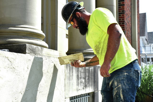 Cody Willoughby | Troy Daily News Subcontractor Jordan Burns of Spectrum Service, LLC, smooths out the newly renovated facade of the Troy Post Office. Due to water damage, the stucco facade of the post office was removed. Workers touched up the mortar between the brick, and resurfaced the facade with exterior insulation and finish system (EIFS) in place of the previous stucco finish.