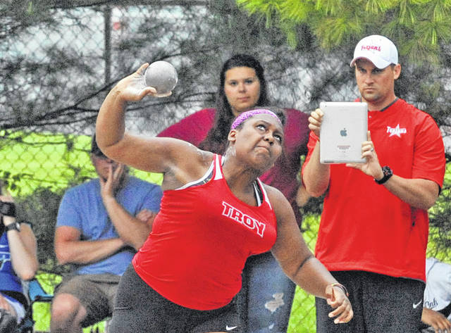 Josh Brown | Troy Daily News file photo Troy throwing coach Aaron Gibbons (right) gets film of Troy graduate Alaura Holycross throwing the shot put at the Division I district track and field meet.