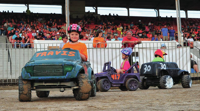 Mike Ullery | Daily Call Power Wheels Derby participants Travis Chaney,9, Haley Chaney,7, and Dylan Barnhart, 6, fight it out in front of the grandstand at the Miami County Fair on Thursday. The Chaneys are from Springfield while Barhart is from Covington.
