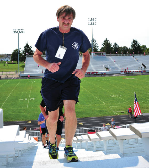 Casstown firefighter Rick Knife, wearing a nametag of a fallen New York City fireman, makes his way to the top of Troy Memorial Stadium during the 1st Freedom Climb in 2017.