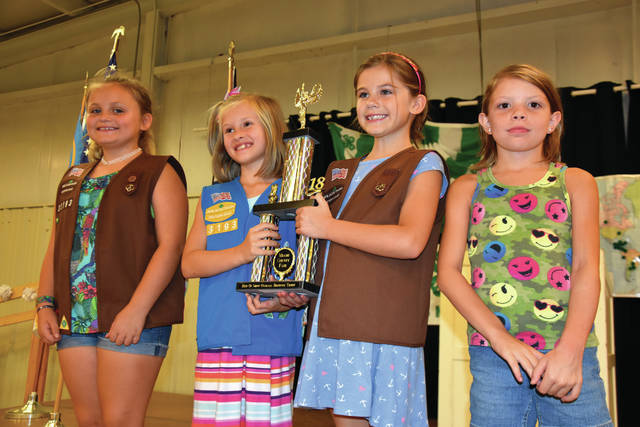 Cody Willoughby | Troy Daily News From left, Alexa Coffey, Elaina Giblin, Audrey Starnes, and Valeria Griffieth accept the Best of Show Overall Brownie Troop trophy for Brownie Troop 33193 during the Girl Scouts Award Ceremony on Monday at the 2018 Miami County Fair.