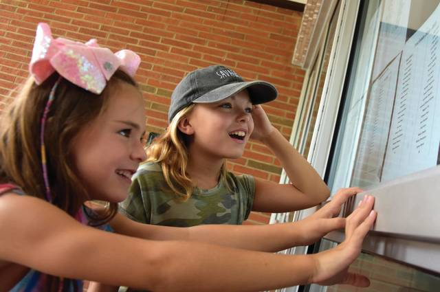 Cody Willoughby | Troy Daily News Maggie and Josie Line, 6 and 10, of Troy check out their new class rosters on Friday outside Hook Elementary School in Troy. The 2018-19 school year is set to commence throughout the Troy City School district on Wednesday, Aug. 22.