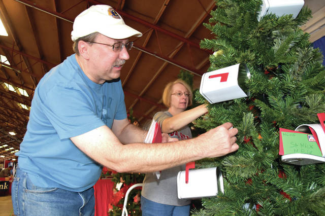 "Cody Willoughby | Troy Daily News Steve and Patty Kaplin decorate a ""letters from Santa""-themed tree during the Christmas tree decorating contest on Friday, held at the merchants' building during the 2018 Miami County Fair."