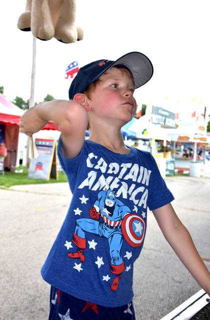 Cody Willoughby | Troy Daily News Eli Ross, 6, of Piqua flings darts at the midway games on Friday at the 2018 Miami County Fair.