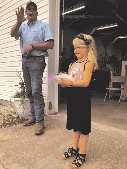 Local auctioneer Scott Pence takes bids outside of the Art Hall at the annual Best in Show baked goods sale on Saturday. Emma Brumbaugh, 5, of Tipp City, won Best in Show for her banana bread. Proceeds benefit the baker and the Art Hall at the Miami County Fair.