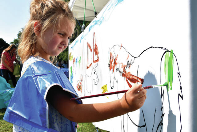 "Cody Willoughby | Troy Daily News Haley Matheny, 5, of Pleasant Hill adds strokes to the community painting during ""Kids Day"" on Monday at the 2018 Miami County Fair."