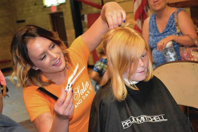 "Cody Willoughby | Troy Daily News Stephanie Staley of Troy Salon and Day Spa provides a haircut to Payton Hicks, 7, of Troy during the seventh annual ""Back to School Bash"" at Lincoln Community Center on Sunday in Troy."