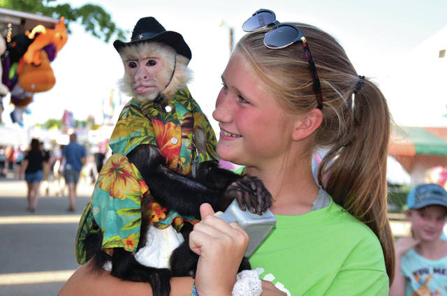 Cody Willoughby | Troy Daily News Korrah Patton, 14, of Casstown gets acquainted with Tiko the monkey on Monday during the 2018 Miami County Fair. The fair is set to continue through Thursday.