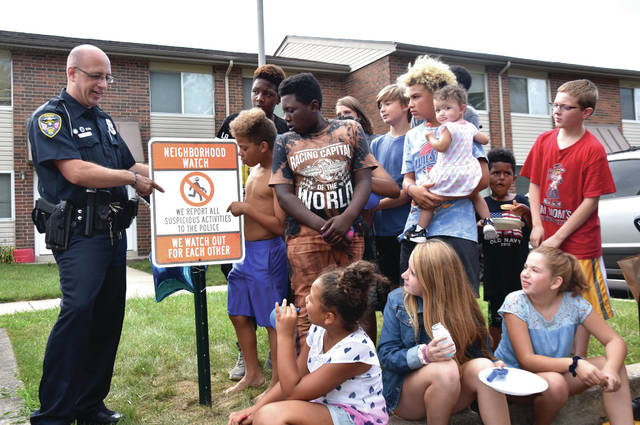 "Cody Willoughby | Troy Daily News Patrolman Joel Misirian discusses the new 'Neighborhood Watch' signs recently implemented at Garden Manor Community Apartments with various young residents during a police-community engagement meeting on Tuesday in Troy. The event was held in conjunction with ""National Night Out,"" and was one of many neighborhoods involved in the outreach."