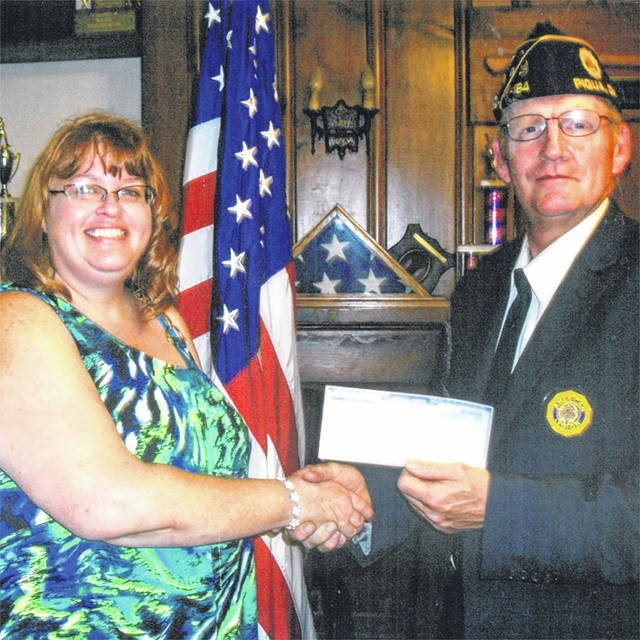 Provided photo Angel Turner accepts a scholarship from Piqua American Legion Post Commander Steve Mullikins.