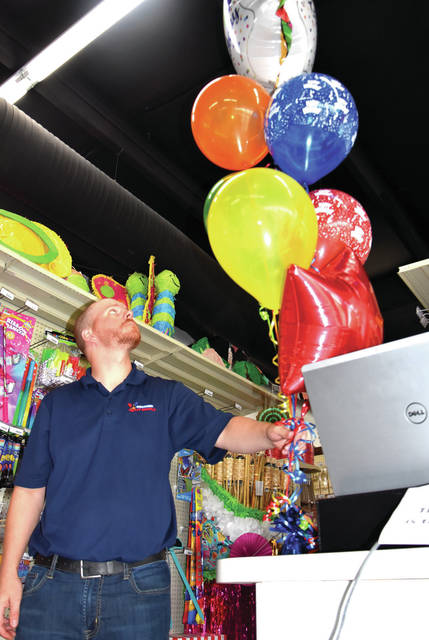 Cody Willoughby | Troy Daily News General Manager Jarrod Stewart places balloons on the front counter at Special Occasions Party Supply, now open for business on West Main Street in Troy.