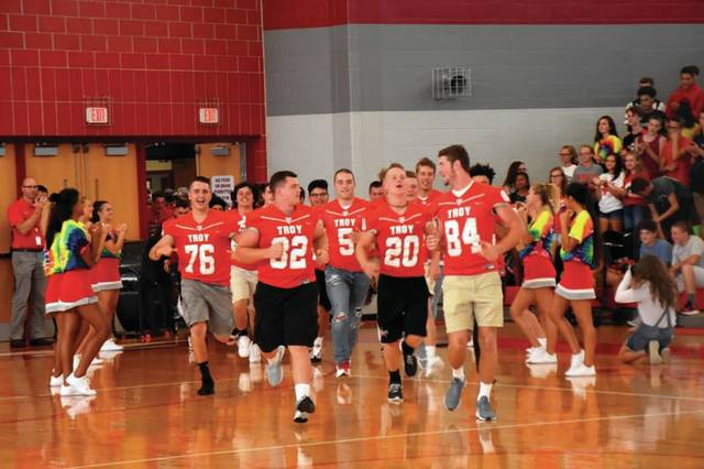 Cody Willoughby | Troy Daily News The Troy Trojans charge the gymnasium at Troy High School during a season-opening pep rally on Friday, ahead of the first game of the season against Belmont at Troy Memorial Stadium.